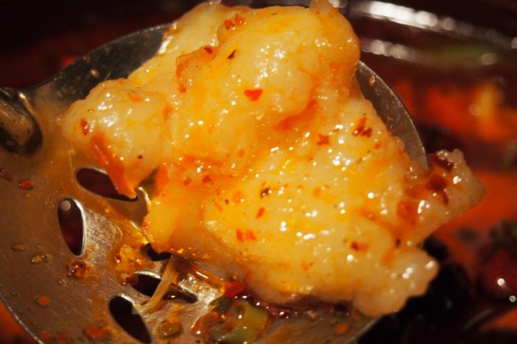 水、豆板醤、あっさり豚骨がベースの混合スープに沈む、魚の切り身