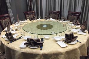 桌上摆放着碗、盘子、小蝶、筷子、玻璃酒杯和折叠各种花样的餐巾。